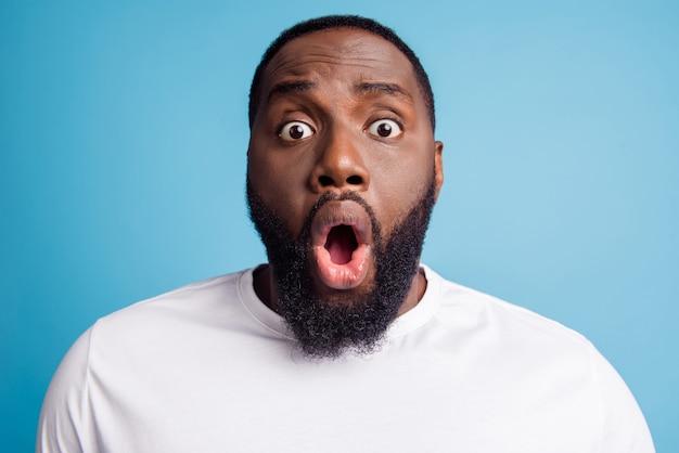 Foto eines verängstigten nervösen unruhigen jungen mannes mit offenem mund, der ein weißes t-shirt auf blauem hintergrund trägt