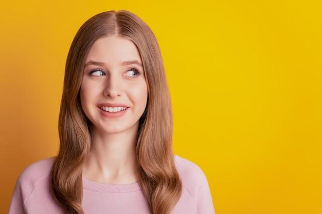 Foto eines verträumten inspirierten mädchens, das lächelt, sieht leer aus auf gelbem hintergrund
