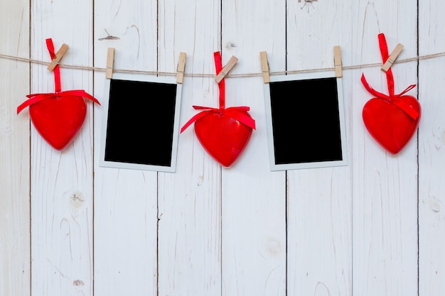 Foto-frame leer und rotes herz hängen auf weißem holz hintergrund mit platz