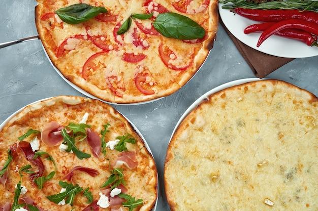 Foto für das pizzeria-menü. drei verschiedene pizzen margarita, vier käse und mit jamon .. draufsicht. essen flach lag