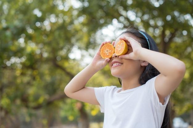 Foto glückliches kleines asiatisches mädchenkind stehend, das vorderzähne mit großem lächeln zeigt. bedeckende augen mit orange mit abstraktem verschwommenem laub und hellem sommer.
