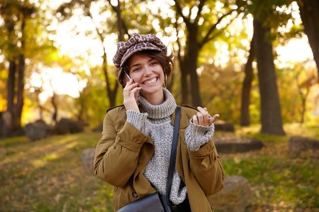 Foto im freien der attraktiven fröhlichen jungen kurzhaarigen brünetten frau, die glücklich nach vorne schaut und breit lächelt, während sie nettes telefongespräch hat und über park am sonnigen herbsttag geht