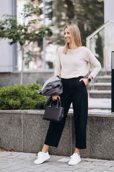 Foto im freien der blonden dame, die auf architekturhintergrund im herbsttag aufwirft. schließen sie herauf mode streetstyle-porträt. tragen sie dunkle freizeithose, cremigen pullover und grauen mantel oder jacke. modekonzept.