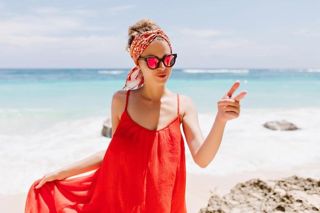 Foto im freien des anmutigen kaukasischen mädchens trägt funkelnde brille während der ruhe nahe ozean. porträt der reizenden gebräunten frau in der roten kleidung, die am wilden strand kühlt.