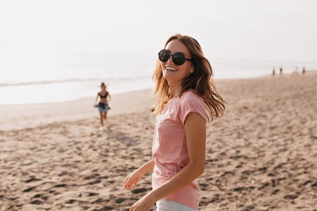Foto im freien des glücklichen jungen weiblichen modells im sommer-t-shirt, das gegen blauen himmel und sandstrandfrau steht, die spaß an einem sommertag hat