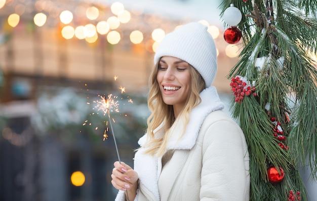 Foto im freien des jungen schönen glücklichen lächelnden mädchens, das wunderkerze hält und auf straße geht. frau, die stilvolle winterkleidung trägt. weihnachten, neujahr, konzept.