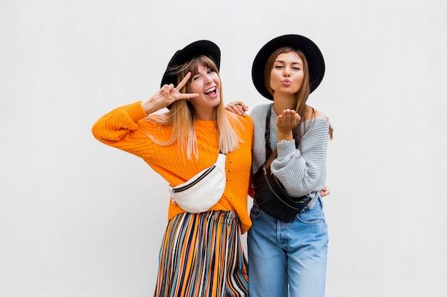 Foto im freien von zwei fröhlichen freundinnen, die große zeit zusammen verbringen, die auf weiß aufwirft