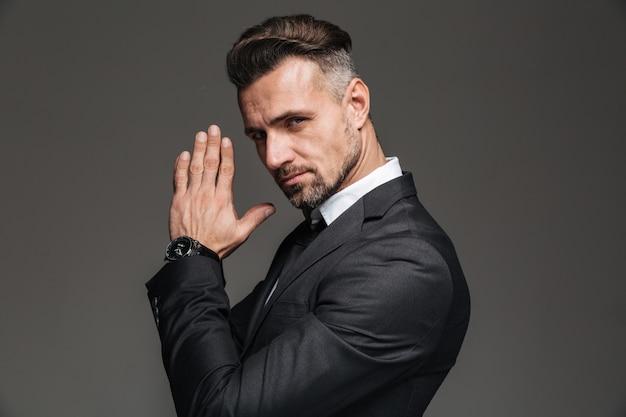 Foto im profil des eleganten erwachsenen mannes 30s im schwarzen anzug, der auf kamera mit schwierigem anblick und händchenhalten zusammen betrachtet, lokalisiert über dunkelgrau