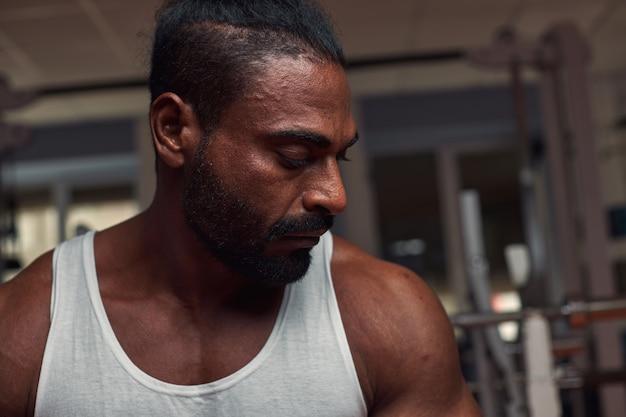 Foto im profil eines attraktiven sportlers, der im fitnessstudio steht und ein hochwertiges foto herunterschaut