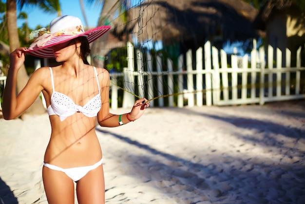 Foto im retro-stil des sexy modellmädchens im weißen bikini mit volleyballnetz am strand und an den palmen hinter schönem sonnenuntergang