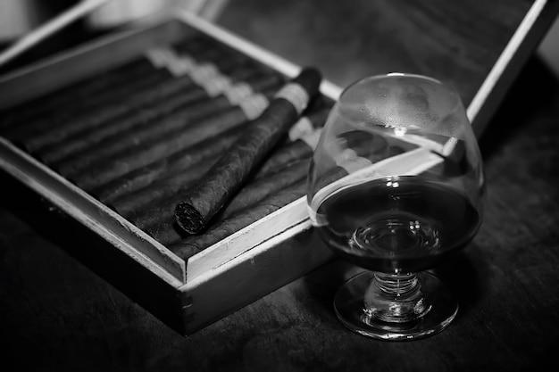 Foto im retro-stil einer großen kiste kubanischer zigarren auf einem holztisch in einer ansehnlichen verpackung