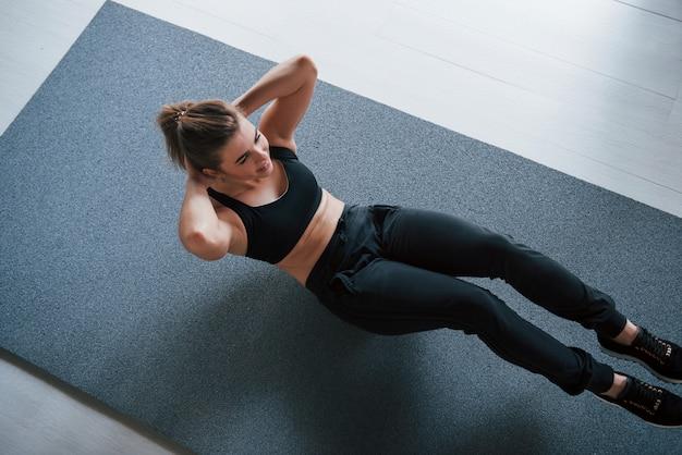 Foto in bewegung. bauchmuskeln auf dem boden im fitnessstudio machen. schöne weibliche fitnessfrau