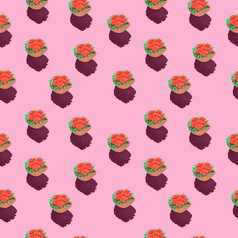 Foto in form eines nahtlosen musters rote blumen in einem grünen korb mit schatten auf einem farbigen rosa
