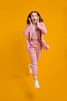 Foto in voller größe einer jungen glücklichen, schockierten, überraschten frau, die vor aufregung einzeln auf gelbem hintergrund springt, rosa anzug trägt und die hände auf die wangen hebt