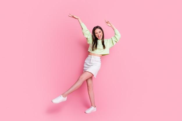 Foto in voller größe von attraktiver funky dame aufgeregt tanzdisco hit jugendparty tänzerin tragen lässige grüne ernte pullover nackte bauchjeans kurzen rock schuhe isoliert rosa pastellfarbenen hintergrund