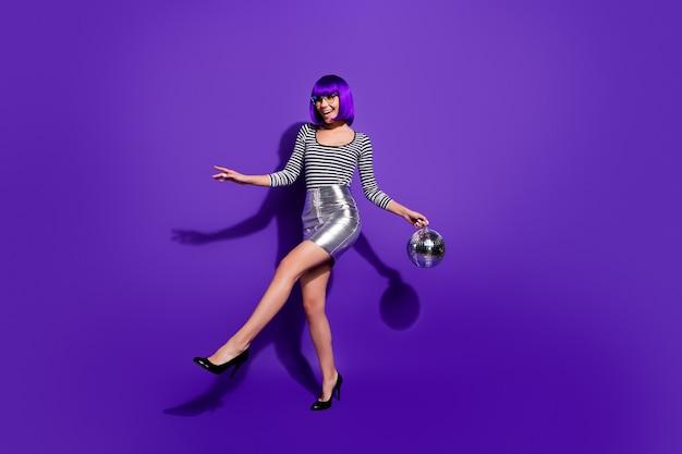 Foto in voller größe von fröhlichen jugendlichen halten spiegelkugel glühen glitzer bewegen tragen brillen brillen isoliert über lila violetten hintergrund