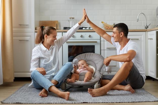 Foto in voller größe von positiven, drei personen mama papa kleines kind mädchen oder junge in türsteher, eltern machen hände dach und genießen es, auf dem boden in der hellen küche zu sitzen, drinnen.