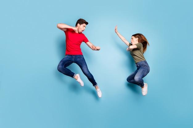 Foto in voller größe von verrückten verrückten zwei menschen verheirateten mann frau sprungzug kickboxen übung kick entscheiden, wer am besten tragen grün rot t-shirt jeans über blau farbe hintergrund isoliert