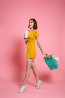 Foto in voller länge der niedlichen erstaunten frau im gelben kleid, das getränk und bunte einkaufstaschen hält, beiseite schauend