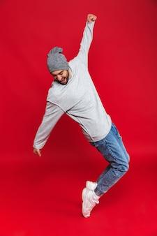 Foto in voller länge des freudigen mannes 30s in der freizeitkleidung lächelnd und springend isoliert