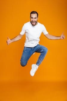 Foto in voller länge des fröhlichen kerls im t-shirt und in den jeans, die springen und spaß haben, isoliert