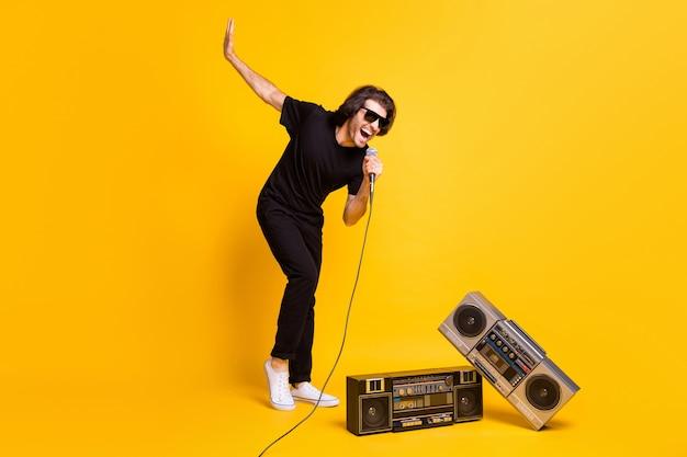 Foto in voller länge des jungen mannes, der das mikrofon mit offenem mund hält, heben die hand zwei retro-radio tragen schwarze t-shirt-hose weiße turnschuhe brille isoliert gelber hintergrund