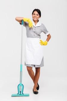 Foto in voller länge des lächelnden brünetten dienstmädchens in uniform und gummihandschuhen, die im stehen auf mopp gelehnt wurden