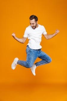 Foto in voller länge des lächelnden kerls im t-shirt und in den jeans, die springen und spaß haben, isoliert
