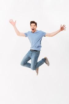 Foto in voller länge des lustigen mannes 30s im lässigen t-shirt und in den jeans springend mit den armen, die sich übergeben, lokalisiert über weißer wand