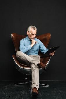 Foto in voller länge des reifen intelligenten mannes, der im büro arbeitet, während auf modernem sessel sitzt, lokalisiert über schwarzer wand