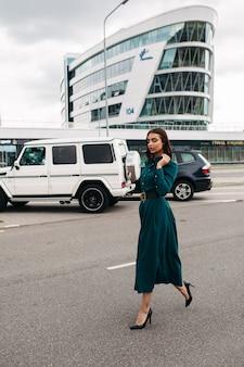 Foto in voller länge einer hübschen brünetten frau in einem langen smaragdgrünen kleid mit knöpfen und schwarzen lederabsätzen, die selbstbewusst die straße entlang gegen moderne gebäude und autos laufen.
