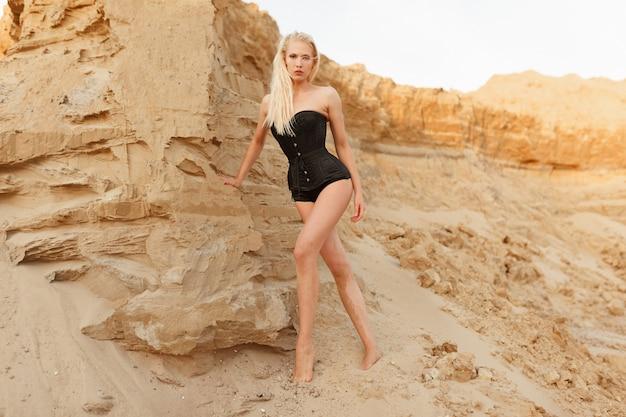 Foto in voller länge einer schlanken, sexy jungen frau mit langen blonden haaren im schwarzen body, blick in die kamera, sandklippenhintergrund.