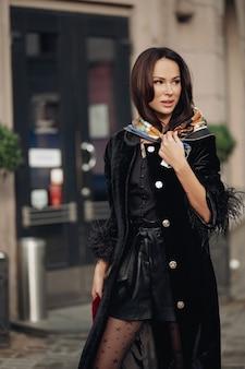 Foto in voller länge einer schönen eleganten frau, die auf der straße geht, während sie einen seidenschal auf dem kopf trägt. beauty- und modekonzept