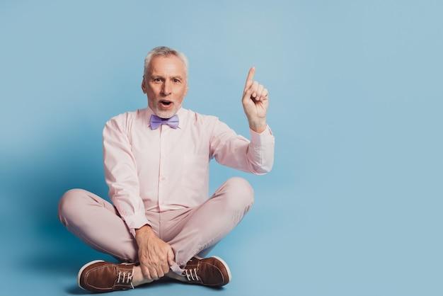 Foto in voller länge eines gealterten mannes, der auf dem boden sitzt, hat eine idee, die auf blauem hintergrund isoliert ist