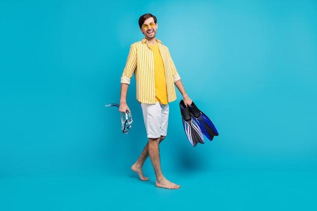 Foto in voller länge, positiver kerl, tourist, gehen sie am strand spazieren, versuchen sie wassersport, halten sie die maske, die schutzbrille, die röhrenflossen, tragen sie ein gelb gestreiftes hemd, das weiße kurze nackte füße isoliert blauer hintergrund