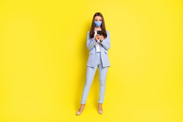 Foto in voller länge smm arbeiter mädchen atemmaske verwenden smartphone sms eingeben covid news post tragen blaue blazerjacke hose hose high-heels isoliert hell glänzender hintergrund