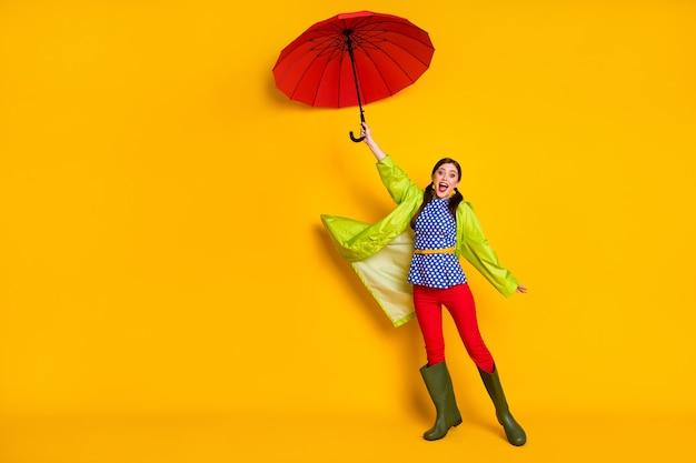 Foto in voller länge verrückt positives mädchen halten luft wind schlag fliegen sonnenschirm beeindruckt regen sturm wetter tragen blau gepunktete bluse hose gummischuhe isoliert heller glanz farbhintergrund