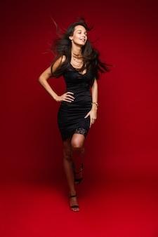 Foto in voller länge von atemberaubender brünetter junger dame mit beweglichen langen haaren im schwarzen kleid und hochhackigen sandalen auf roter wand herein