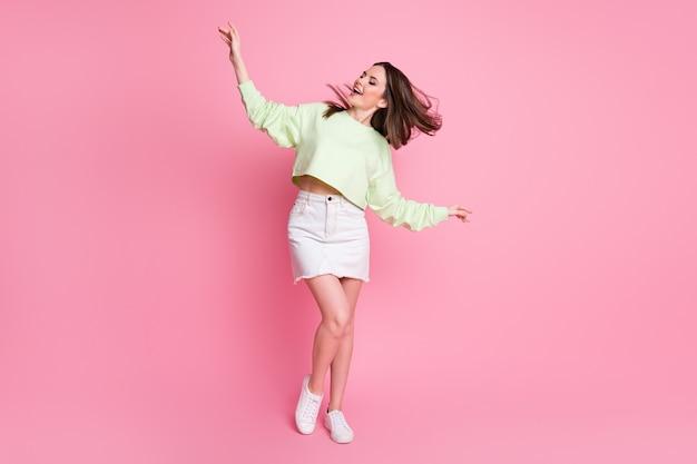 Foto in voller länge von attraktiver dame aufgeregt tanz disco hit jugendparty frisur flug tragen lässige grüne ernte pullover nackte bauchjeans kurzen rock schuhe isoliert rosa farbe hintergrund