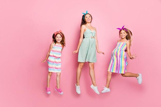 Foto in voller länge von charmanten drei personen, die das stirnbandrockkleid tragen, lokalisiert über rosa hintergrund