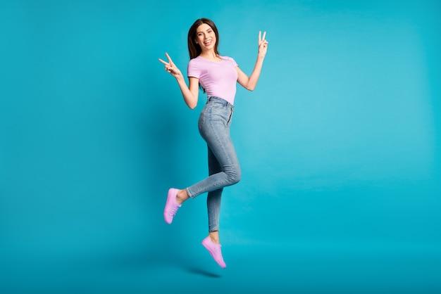 Foto in voller länge von charmanten mädchen jump show v-zeichen tragen rosa t-shirt sneakers jeans isoliert blauer hintergrund