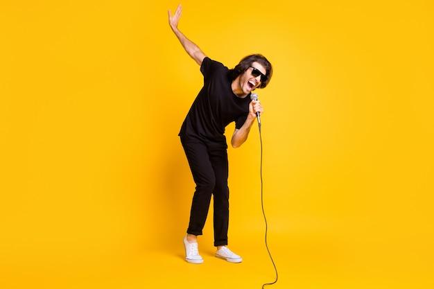 Foto in voller länge von einem jungen mann mit mikrofon singen mit offenem mund heben hand tragen schwarze t-shirt-hose weiße turnschuhe sonnenbrille isoliert gelber farbhintergrund
