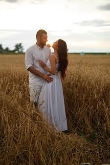 Foto in voller länge von einem romantischen paar in weißer kleidung, das sich bei sonnenuntergang im weizenfeld umarmt.