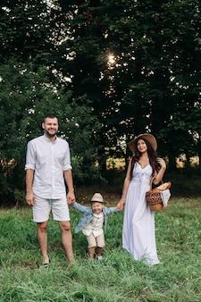 Foto in voller länge von einem vater und einer mutter, die die hände ihres sohnes halten, die im sommerpark in den bäumen stehen. frau in hut und kleid hält einen braunen korb mit essen für picknick.