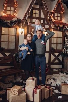 Foto in voller länge von einer glücklichen familie von mutter, vater und zwei söhnen, die in einem dekorierten raum mit weihnachtsgeschenken unter schneefall stehen
