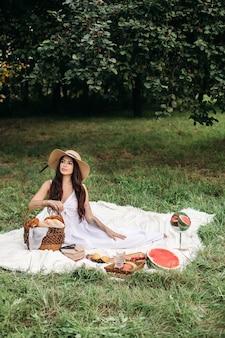 Foto in voller länge von einer wunderschönen brünetten dame in sommerhut und weißem kleid, die auf der decke mit einem korb der bäckerei und anderen nahrungsmitteln um sie herum auf der decke im sommerpark sitzt.