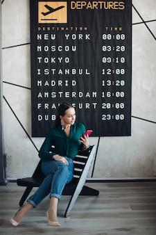 Foto in voller länge von eleganter geschäftsfrau in smart casual mit handy, die auf ihren flug gegen abflugplakat wartet.