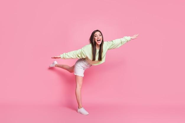 Foto in voller länge von enthusiastischen, fröhlichen teenager-mädchen, die hand heben, die beine beeindruckt haben, gymnastik schlucken übung tragen gut aussehende outfit-schuhe einzeln auf pastellfarbenem hintergrund