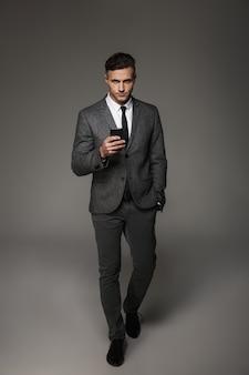 Foto in voller länge von ernstem geschäftsmann, der sachlichen anzug und krawatte trägt, die streng mit smartphone in der hand suchen, lokalisiert über graue wand