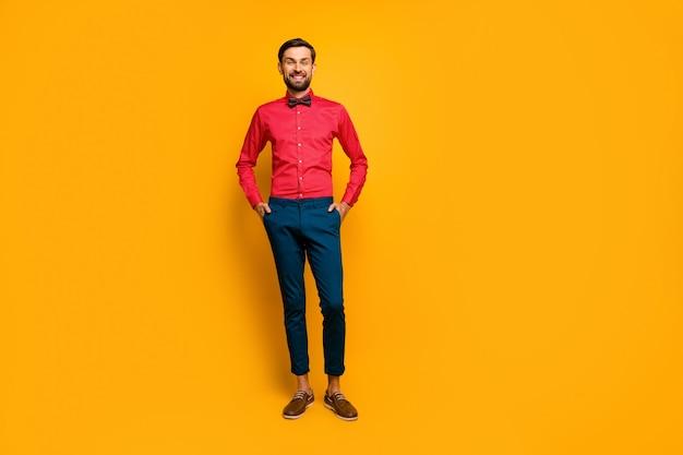 Foto in voller länge von erstaunlichen macho mann stehend gute laune freundlich strahlend lächelnd tragen stilvolles rotes hemd mit fliege blaue hosen schuhe